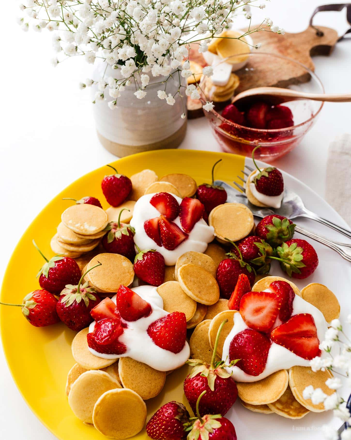 This fluffy mini strawberry shortcake pancake recipe is perfect for summer. Super cute mini silver dollar vanilla pancakes topped with juicy strawberries and softly whipped cream. Like a strawberry shortcake for breakfast! #strawberries #strawberry #strawberrypancakes #strawberrypancake #strawberryshortcake #strawberryshortcakes