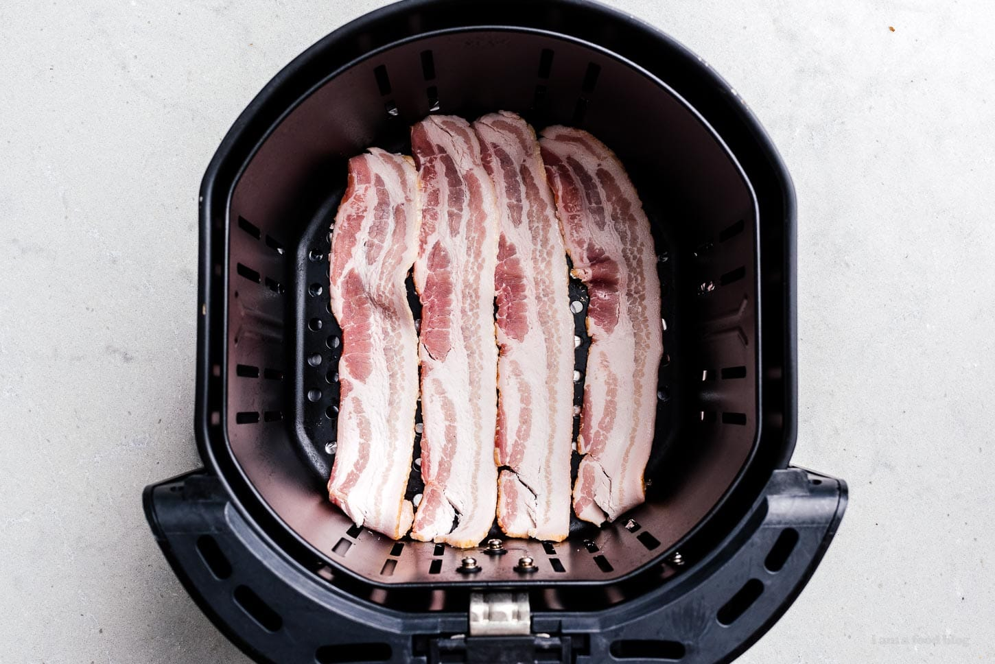 bacon in an air fryer basket | www.iamafoodblog.com